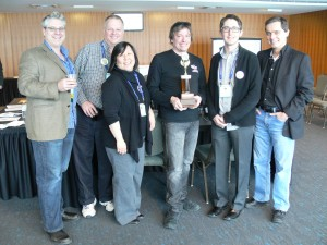2014 GOHCBC judging panel with winning brewer James Grant (The Blue Elephant) holding the coveted 'Bottomless Cup' in Niagara Falls during the OFVC – L-R: Jason Deveau, Jeff Stevens, Laura Takata, James Laurent, Al Sutherland, and Michael Ligas